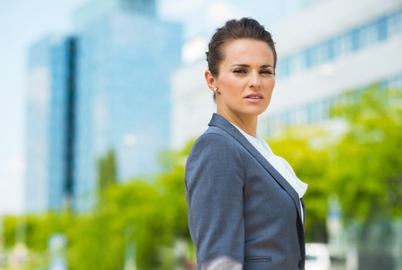 certitude: Into the ultra-modern business trends. Portrait of confident business woman in modern office district