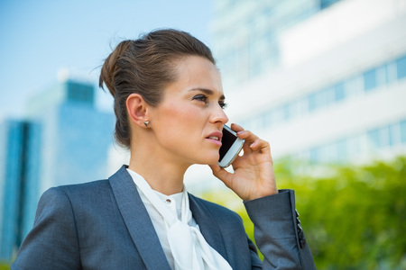 Into the ultra-modern business trends. Portrait of confident business woman in modern office district talking smartphone