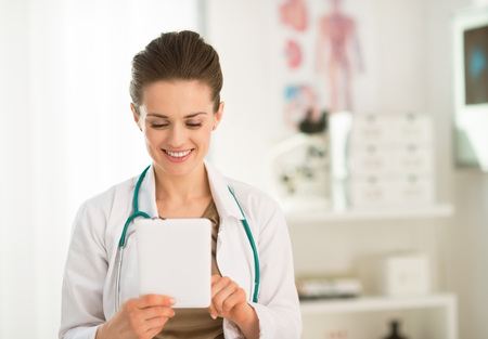 topicality: Modern health care. Happy female doctor in the office using tablet PC