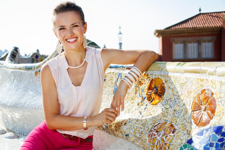 trencadis: Get inspired by Park Guell in your next trip to Barcelona, Spain. Portrait of smiling young woman sitting on the famous trencadis style bench on the main terrace