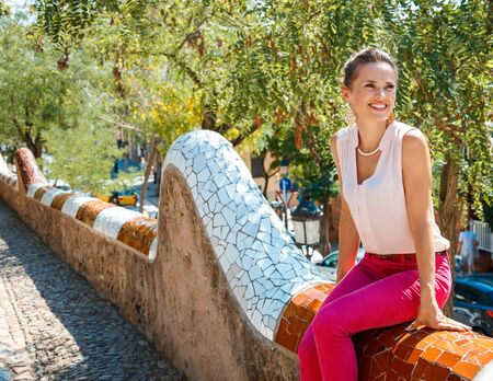 trencadis: Happy young woman sitting on trencadis style fence and looking aside