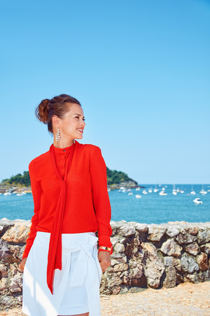 basque woman: Luxury weekend retreat. Happy young woman in bright blouse standing in front of the beautiful scenery overlooking lagoon with yachts and looking aside
