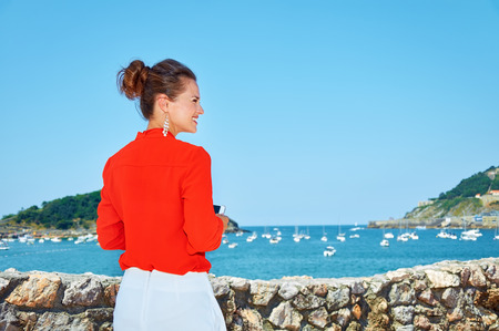 basque woman: Luxury weekend retreat. Seen from behind woman in bright blouse with cellphone standing in front of the beautiful scenery overlooking lagoon with yachts and looking aside