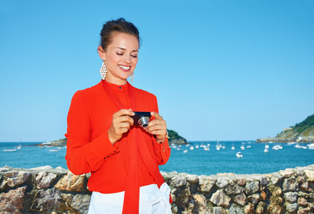 basque woman: Luxury weekend retreat. Happy young woman in bright blouse checking photos in digital camera while standing in front of the beautiful scenery overlooking lagoon with yachts