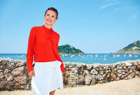 basque woman: Luxury weekend retreat. Smiling young woman in bright blouse standing in front of the beautiful scenery overlooking lagoon with yachts