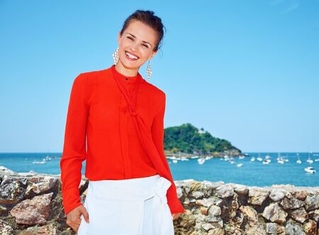 basque woman: Luxury weekend retreat. Portrait of smiling young woman in bright blouse standing in front of the beautiful scenery overlooking lagoon with yachts Stock Photo