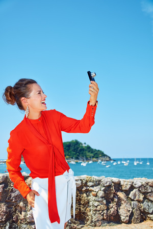 basque woman: Luxury weekend retreat. Smiling young woman in bright blouse taking photo with digital camera while standing in front of the beautiful scenery overlooking lagoon with yachts Stock Photo