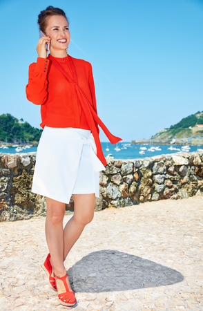 basque woman: Luxury weekend retreat. Full length portrait of happy young woman in bright blouse standing in front of the beautiful scenery overlooking lagoon with yachts and speaking smartphone Stock Photo