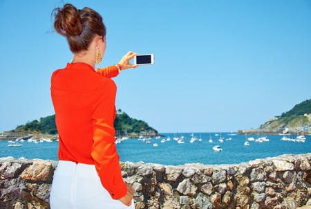 basque woman: Luxury weekend retreat. Seen from behind woman in bright blouse taking photo with smartphone of the beautiful scenery overlooking lagoon with yachts