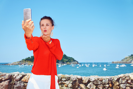 basque woman: Luxury weekend retreat. Happy young woman in bright blouse blowing air kiss and taking selfie in front of the beautiful scenery overlooking lagoon with yachts
