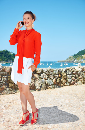 basque woman: Luxury weekend retreat. Full length portrait of smiling young woman in bright blouse standing in front of the beautiful scenery overlooking lagoon with yachts and speaking smartphone Stock Photo