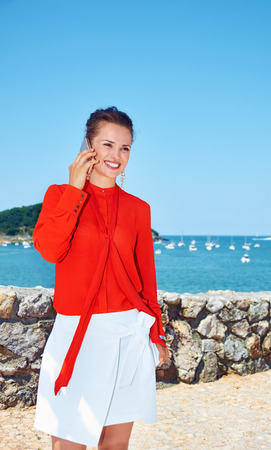 basque woman: Luxury weekend retreat. Smiling young woman in bright blouse standing in front of the beautiful scenery overlooking lagoon with yachts and speaking smartphone Stock Photo