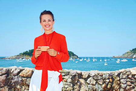 basque woman: Luxury weekend retreat. Portrait of happy young woman in bright blouse standing in front of the beautiful scenery overlooking lagoon with yachts and writing sms Stock Photo