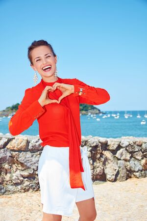 shaped hands: Luxury weekend retreat. Portrait of smiling young woman in bright blouse standing in front of the beautiful scenery overlooking lagoon with yachts and showing heart shaped hands