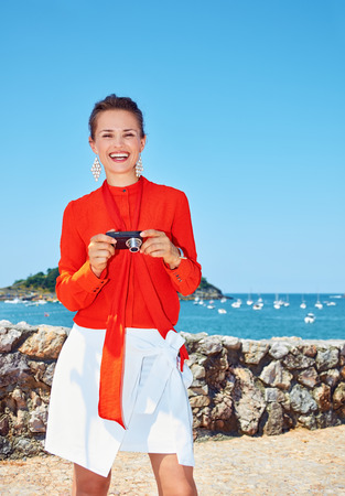 basque woman: Luxury weekend retreat. Happy young woman in bright blouse with digital photo camera standing in front of the beautiful scenery overlooking lagoon with yachts