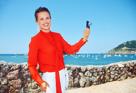basque woman: Luxury weekend retreat. Happy young woman in bright blouse taking photo with digital camera while standing in front of the beautiful scenery overlooking lagoon with yachts