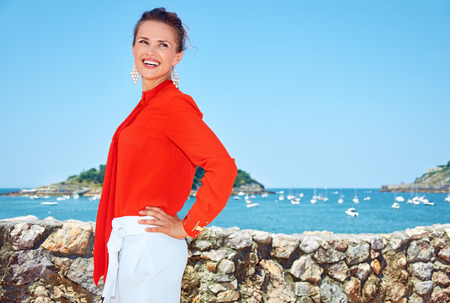 basque woman: Luxury weekend retreat. Portrait of smiling young woman in bright blouse standing in front of the beautiful scenery overlooking lagoon with yachts and looking aside Stock Photo