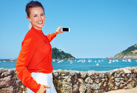 basque woman: Luxury weekend retreat. Happy young woman in bright blouse taking photo with smartphone of the beautiful scenery overlooking lagoon with yachts