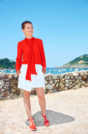 basque woman: Luxury weekend retreat. Full length portrait of smiling young woman in bright blouse standing in front of the beautiful scenery overlooking lagoon with yachts and looking into the distance