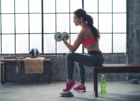 Körper und Geist trainieren im Loft Fitness-Studio. Fitness Frau lifting Hantel in urbanen Loft-Fitness-Studio