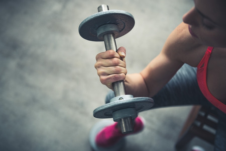 Body and mind workout in loft fitness studio. Closeup on fitness woman workout with dumbbell in urban loft gym Stock Photo