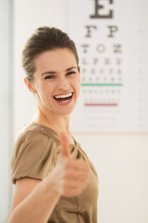 Modern health care. Happy young woman showing thumbs up in front of Snellen chart Stock Photo