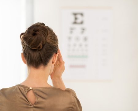 Modern health care. Seen from behind woman testing vision with Snellen chart