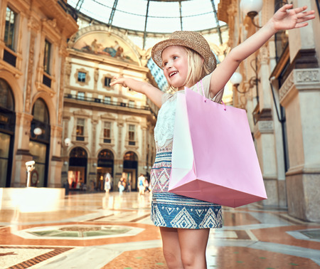 rejoicing: Discover most unexpected trends in Milan. Happy fashion girl with pink shopping bag in Galleria Vittorio Emanuele II rejoicing