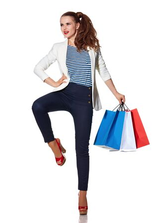 the french way: Shopping. The French way. Full length portrait of young woman with French flag colours shopping bags posing on white background
