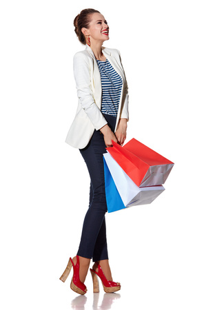 the french way: Shopping. The French way. Full length portrait of excited young woman with French flag colours shopping bags on white background looking aside