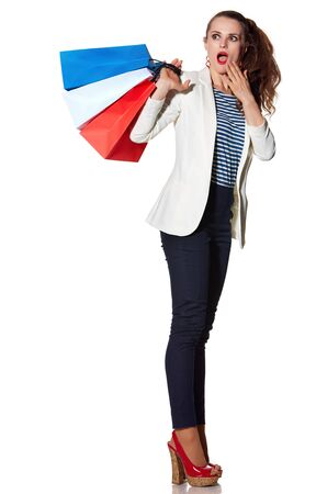 the french way: Shopping. The French way. Full length portrait of surprised young woman with French flag colours shopping bags on white background looking on copy space