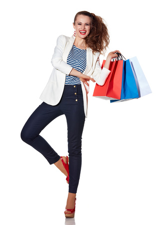 the french way: Shopping. The French way. Full length portrait of smiling young woman with shopping bags on white background