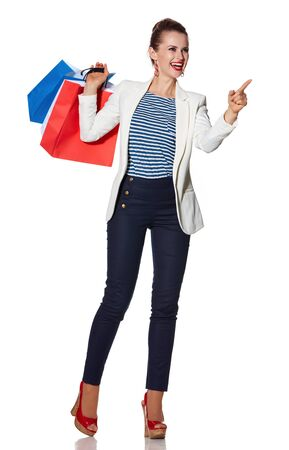 the french way: Shopping. The French way. Full length portrait of smiling young woman with French flag colours shopping bags on white background pointing on copy space Stock Photo