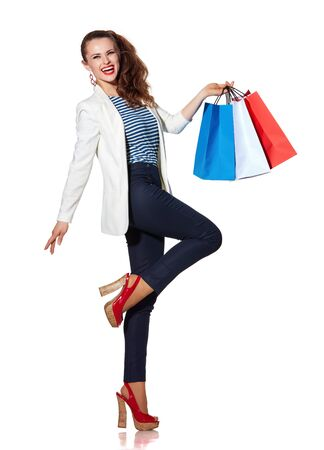 the french way: Shopping. The French way. Full length portrait of smiling young woman with French flag colours shopping bags posing on white background