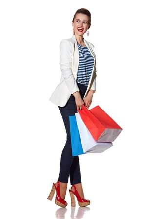 the french way: Shopping. The French way. Full length portrait of excited young woman with French flag colours shopping bags on white background looking on copy space