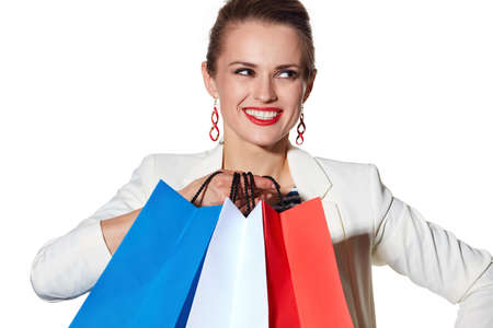 the french way: Shopping. The French way. Close portrait of smiling young woman with French flag colours shopping bags on white background looking aside