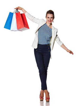 the french way: Shopping. The French way. Full length portrait of happy young woman with French flag colours shopping bags balancing on white background