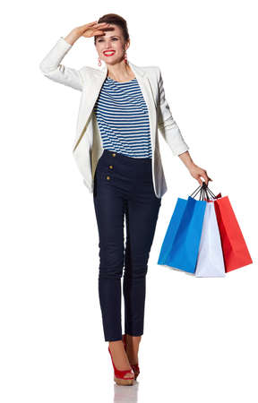 the french way: Shopping. The French way. Full length portrait of happy young woman with French flag colours shopping bags looking into the distance on white background