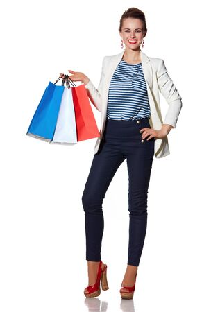 the french way: Shopping. The French way. Full length portrait of smiling young woman with French flag colours shopping bags posing against white background