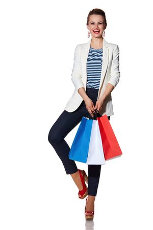 the french way: Shopping. The French way. Full length portrait of happy young woman with French flag colours shopping bags posing against white background Stock Photo