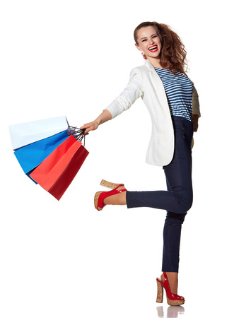 the french way: Shopping. The French way. Full length portrait of smiling young woman with shopping bags posing on white background