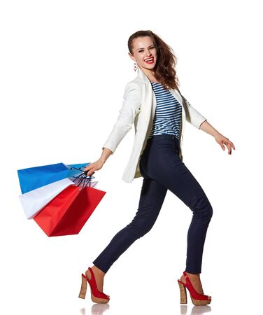the french way: Shopping. The French way. Full length portrait of smiling young woman walking with French flag colours shopping bags on white background