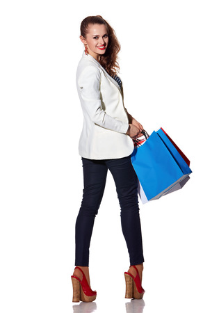 the french way: Shopping. The French way. Full length portrait of happy young woman with shopping bags on white background looking back
