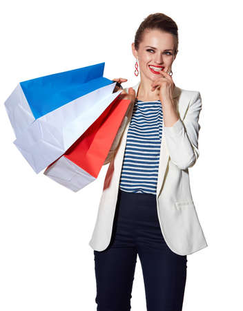 the french way: Shopping. The French way. Portrait of pensive young woman with French flag colours shopping bags on white background Stock Photo