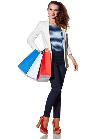 the french way: Shopping. The French way. Full length portrait of happy young woman with French flag colours shopping bags on white background looking on copy space Stock Photo