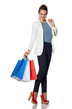 the french way: Shopping. The French way. Full length portrait of smiling young woman with French flag colours shopping bags against white background Stock Photo