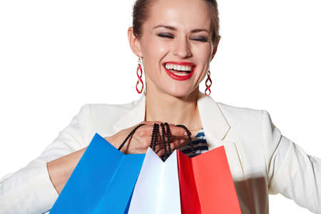 the french way: Shopping. The French way. Close portrait of smiling young woman with French flag colours shopping bags on white background