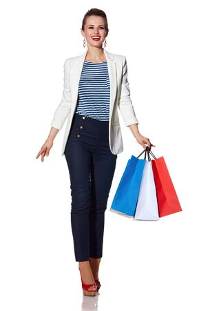 the french way: Shopping. The French way. Full length portrait of happy young woman with French flag colours shopping bags on white background going forward