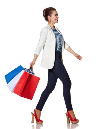 the french way: Shopping. The French way. Full length portrait of happy young woman with French flag colours shopping bags going to the side on white background Stock Photo