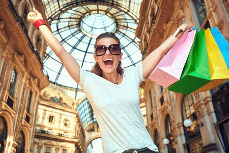 rejoicing: Discover most unexpected trends in Milan. Portrait of happy fashion monger in eyeglasses with colorful shopping bags in Galleria Vittorio Emanuele II rejoicing